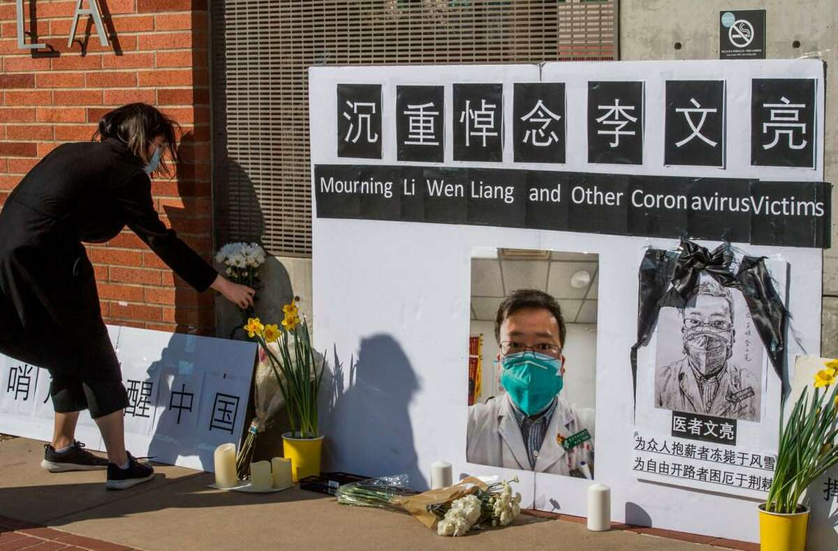 Chinese students and their supporters hold a memorial for Dr Li Wenliang, who was the whistleblower of the coronavirus pandemic that originated in Wuhan, China, and caused the doctor's death in that city, outside the UCLA campus in Los Angeles on February 15, 2020.