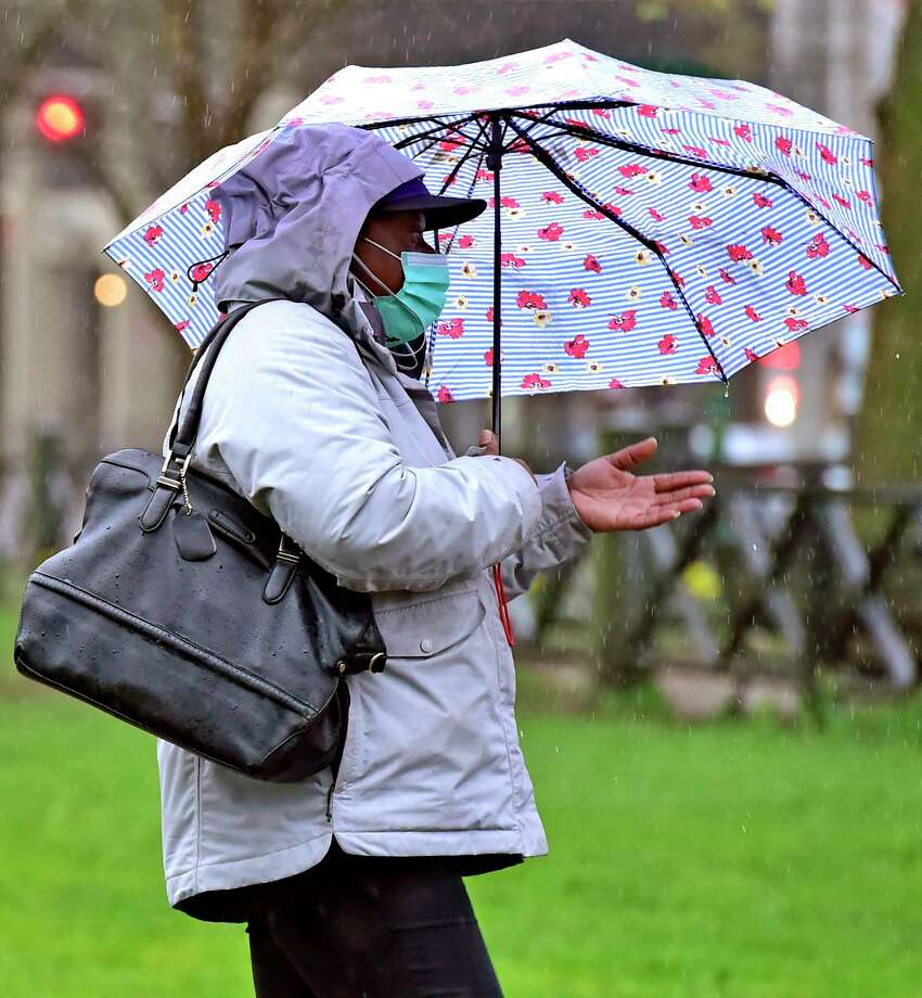 A woman wearing a face mask because of the coronavirus pandemic traverses the New Haven Green Monday in the rain. Photo: Peter Hvizdak / Hearst Connecticut Media / New Haven Register