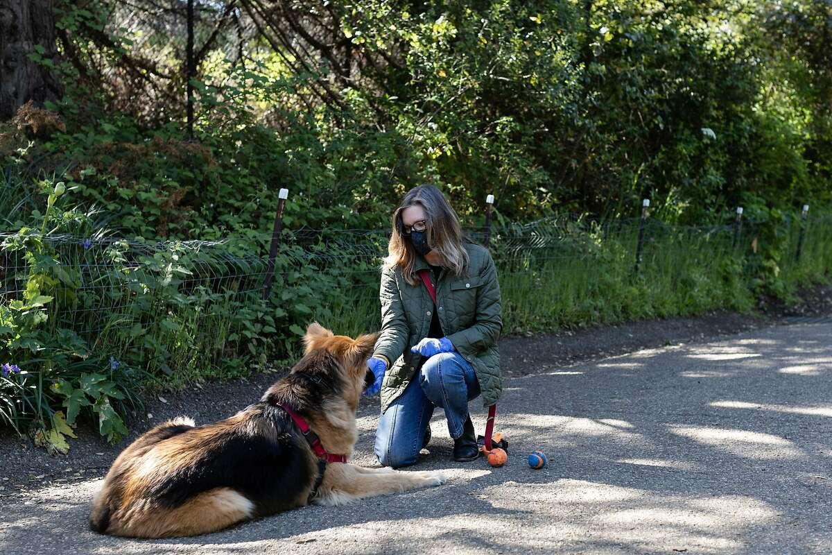 Christina Pappas pets her her dog Lassen at Mountain Lake Park on Monday, April 13, 2020, in San Francisco, Calif.