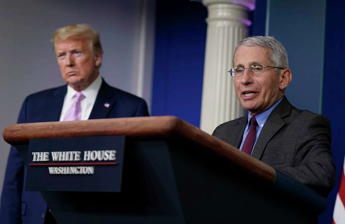 President Donald Trump listens as Director of the National Institute of Allergy and Infectious Diseases Dr. Anthony Fauci speaks during a coronavirus task force briefing at the White House, Friday, April 10, 2020, in Washington.