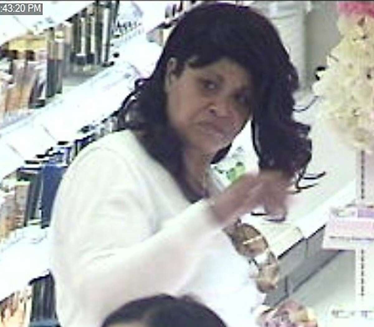 Police released a photo of a woman suspected of robbing a retail store on March 27 and coughing on security employees to get away.