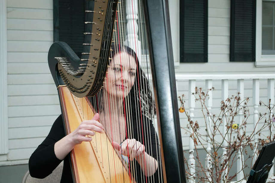 Devon Carpenter plays the harp Sunday at her house in Jacksonville. Carpenter said she wanted to take away some of the stress of people living through the stay-home order and the worldwide coronavirus outbreak. Carpenter was raised in Jacksonville, began playing the harp in high school and has performed with the Jacksonville Symphony Orchestra in addition to traveling the world. Photo: Darren Iozia | Journal-Courier