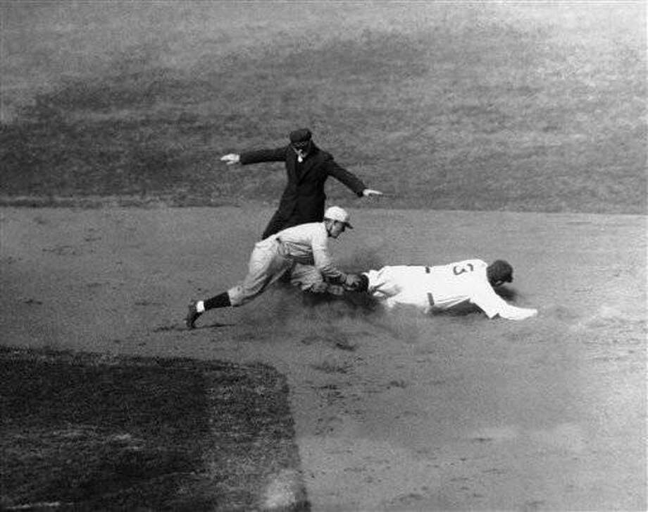 George Herman Babe Ruth slides safely into second base in the first inning of the Yankees Red Sox game in New York, April 14, 1931. Warstler is trying to tag him out, but is too late. (AP Photo)