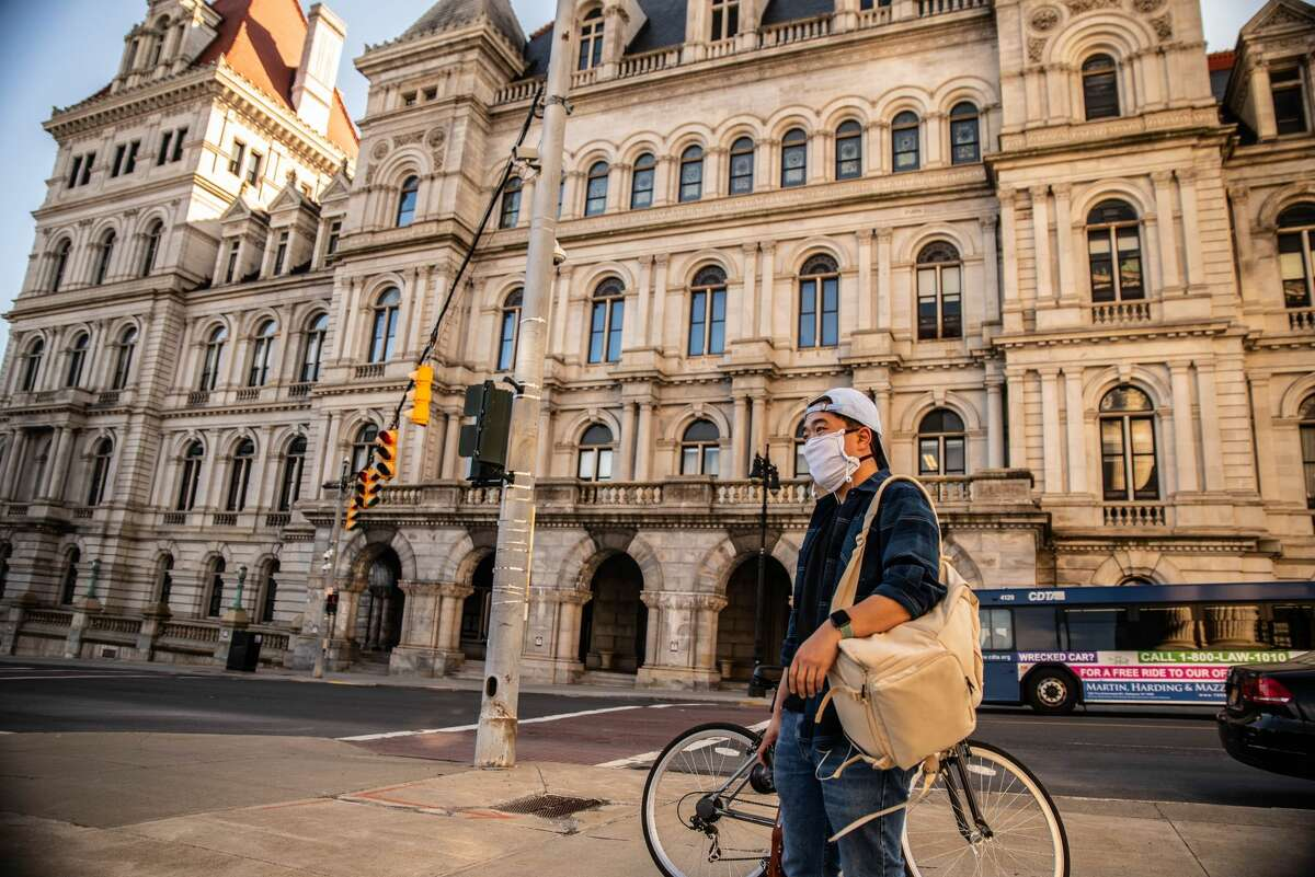 Bicyclist stands outside of the NY State Capitol Monday afternoon wearing a homemade protective mask.