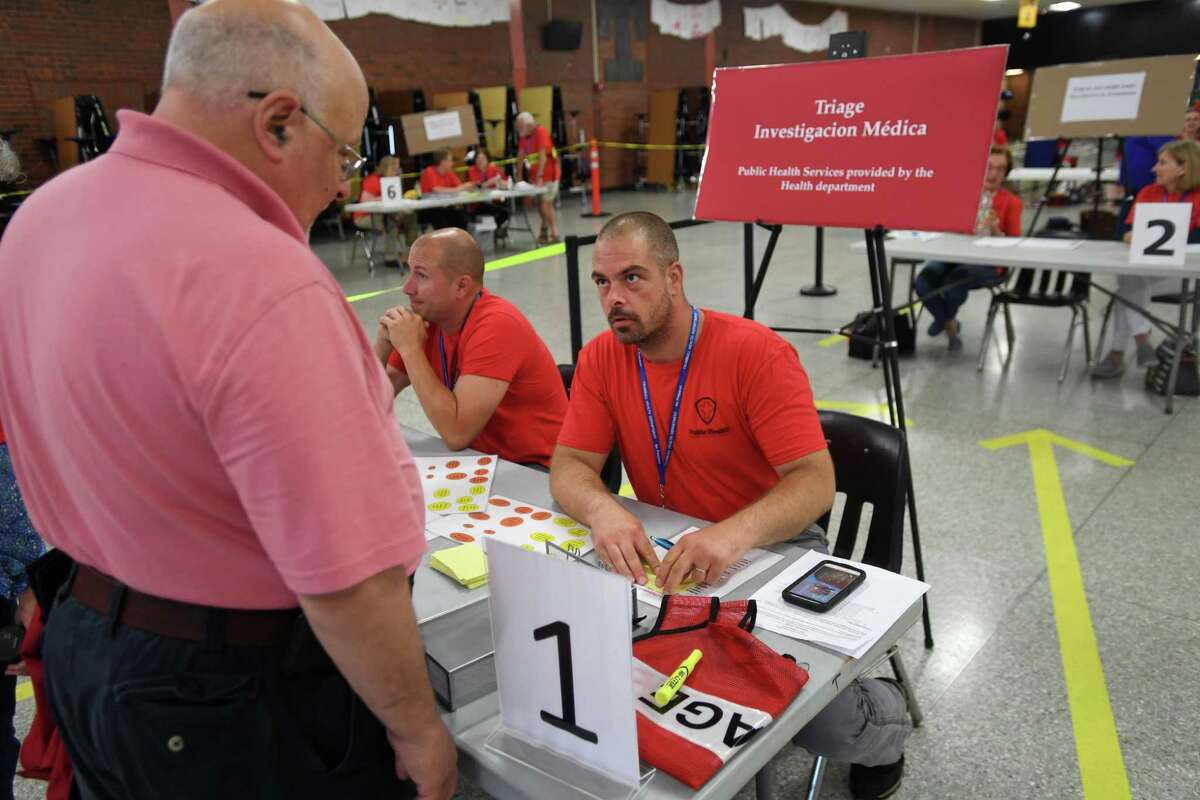 Stamford Community Emergency Response Team volunteer Jon Perelstein, left, checks in at triage with Stratford Health Department staffer Andrew Anderson during at a multiple town drill for the mass dispersing of medication at Trumbull High School in Trumbull, Conn. on Tuesday, June 25, 2019. The drill, featuring Medical Reserve Corps volunteers from Trumbull, Stratford, and Monroe, simulated the dispensing of antibiotics in response to an anthrax incident on a Metro North train.