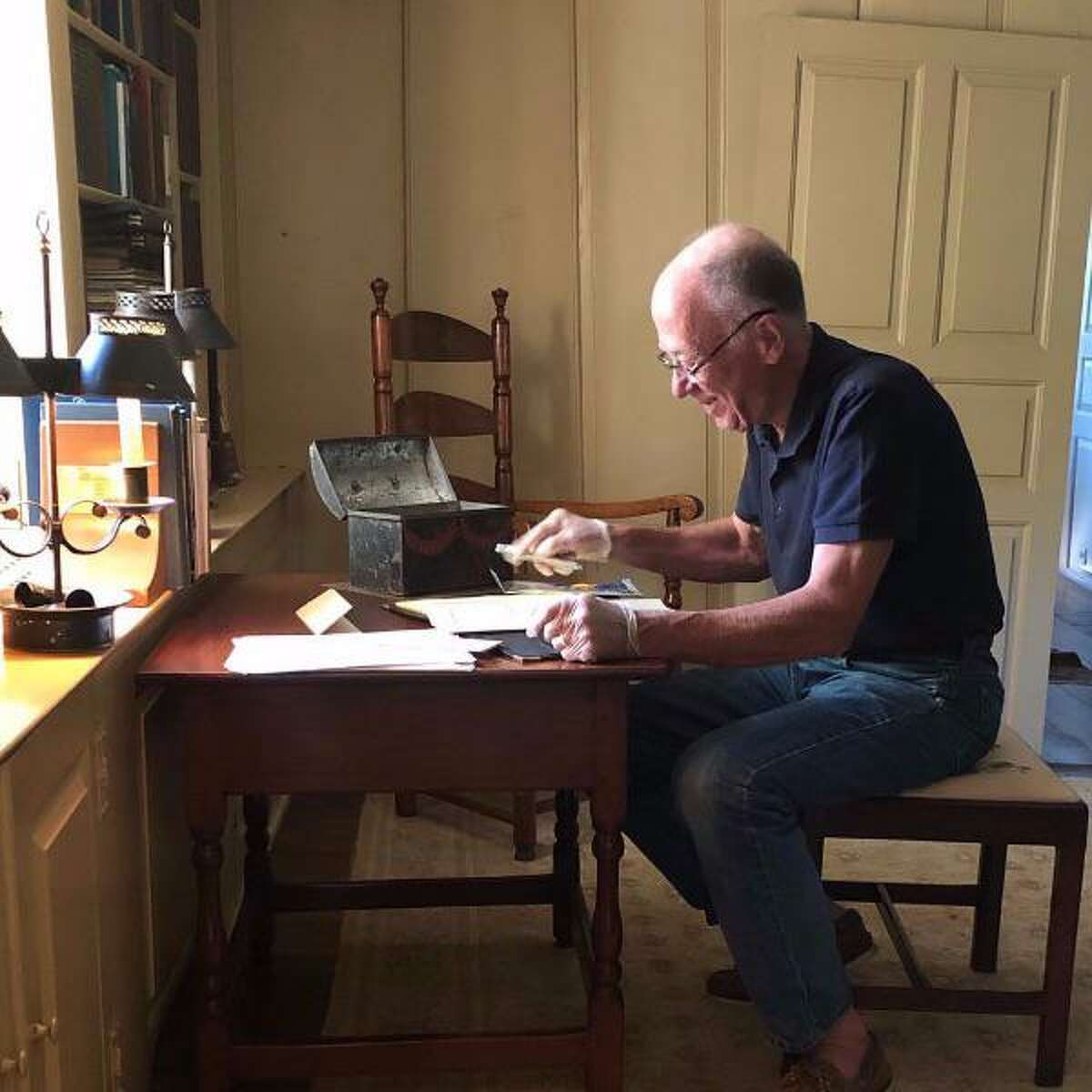 Docent Donn Smith going through old artifacts at the Mather Homestead and making blog posts of them.