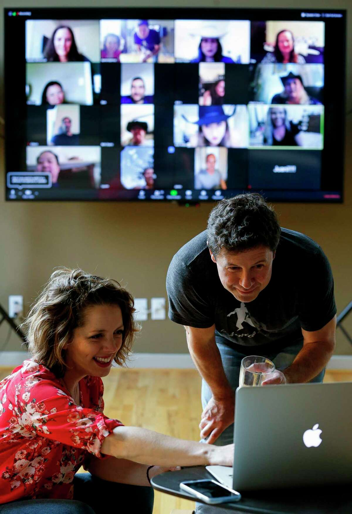 Damon D'Amico, foreground, and his girlfriend Amanda McClure video chat with some of his Country Western dancing student at his home Tuesday, April 7, 2020, in Houston. Among his students are cancer survivors who are immunocompromised, so their Zoom video chats help them reconnect and dance in the middle of the COVID-19 pandemic.