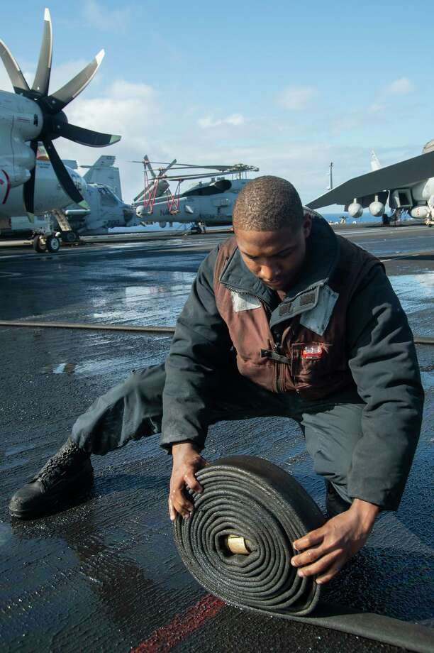 "Airman Hubert Buissereth from Stamford, who is assigned to the ""Seahawks"" of Carrier Command and Control Squadron (VAW) 126, rolls a fuel hose on the flight deck of the Nimitz-class aircraft carrier USS Harry S. Truman (CVN 75) in the Atlantic Ocean on April 11, 2020. The Harry S. Truman Carrier Strike Group is conducting operations in U.S. 6th Fleet to support maritime security operations in international waters, alongside our allies and partners. Truman has spent at least one day underway for 30 of the last 34 months, in direct support of global security around the world. Photo: Photo Courtesy Of U.S. Navy Mass Communication Specialist Seaman Bela Chambers. / Digital"