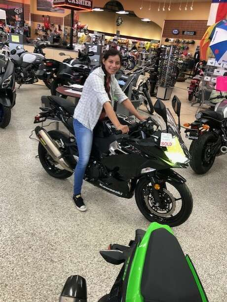 Local nurse Mercedes Suarez smiles with her new motorcycle that was gifted to her by Alamo Cycle Plex after the business learned her old bike was stolen. Photo: Alamo Cycle Plex