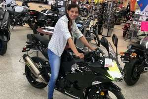 Local nurse Mercedes Suarez smiles with her new motorcycle that was gifted to her by Alamo Cycle Plex after the business learned her old bike was stolen.