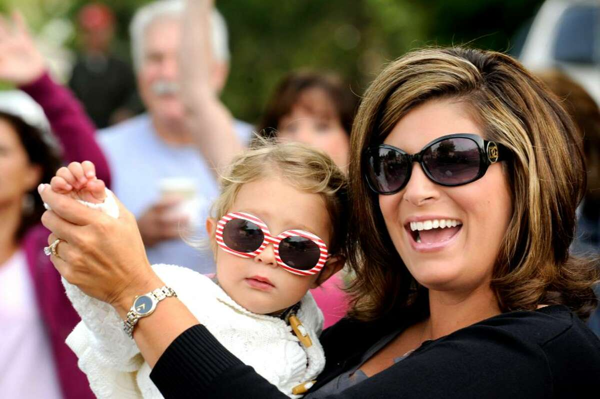 Sophia Pechenko, 2, of Newtown and Chelsa Tomasello, 35, of New Milford wave at passersby along the parade route in the Newtown Labor Day Parade on Monday, Sept. 7, 2009.