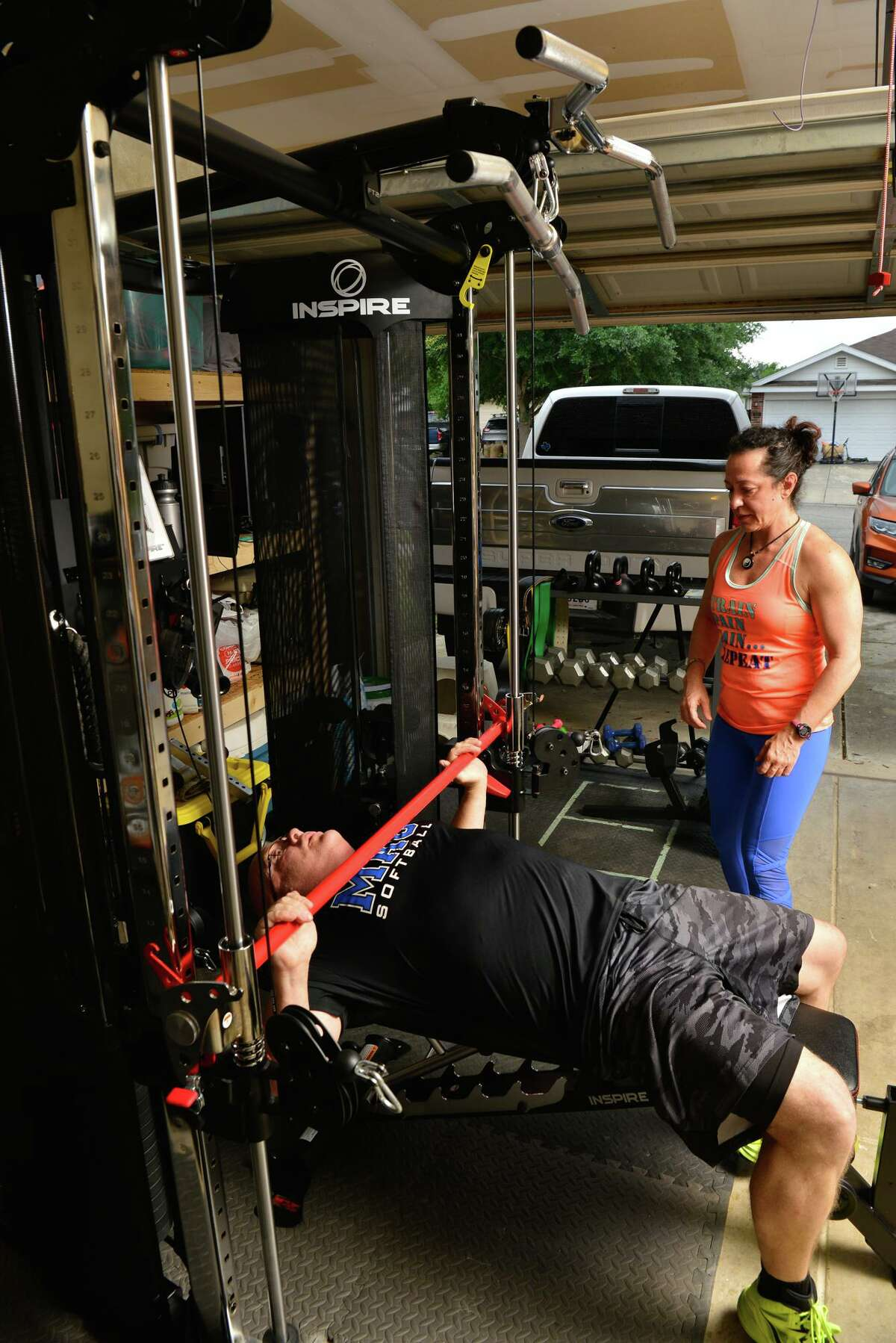 Cristina Cobal watches as her husband Kevin works out on their new functional training machine inside their New Braunfels garage.