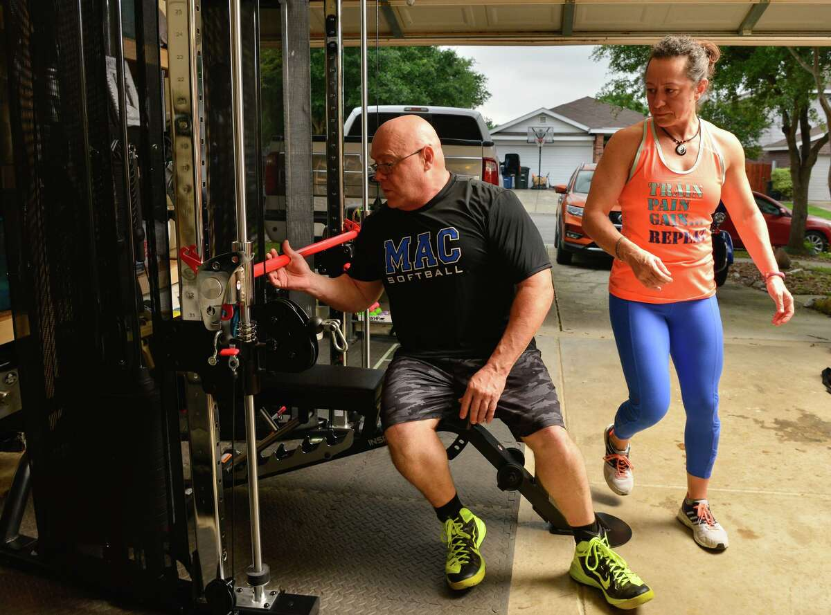 Kevin and Cristina Coble work out in their New Braunfels garage. The Cobles aren't alone in bringing the gym to their home because their usual workout place has closed for the duration.