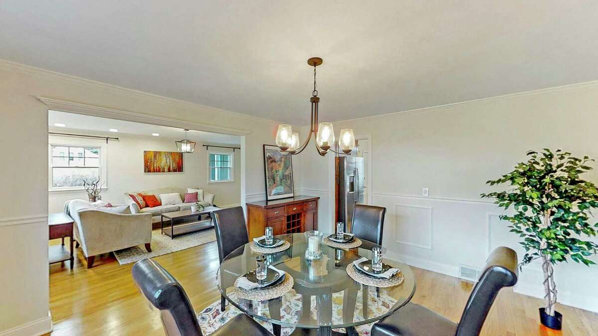 The formal dining room has chair railing and picture frame paneling on the lower walls.