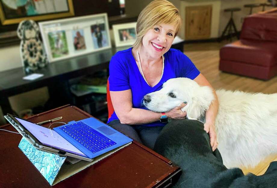 Shelley Park Cluff, vice president of the Midland Board of Realtors, poses for a photo with her dogs as she works from home. (Photo provided/Shelley Park Cuff)