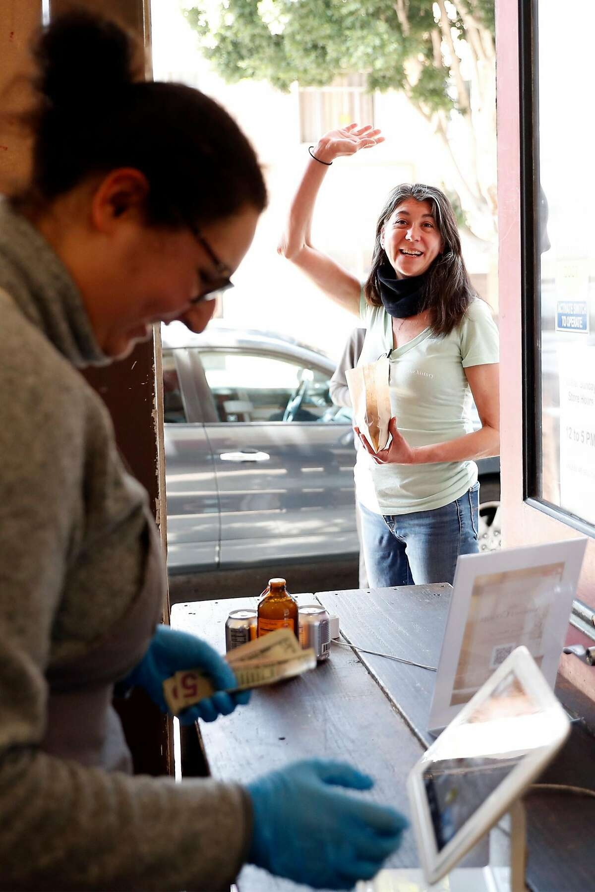After buying cookies, customer Jennifer Garris waves at owner Anthony Lucas as Camille Renaudon smiles at Anthony's Cookies on Valencia Street in San Francisco, Calif., on Monday, April 13, 2020.