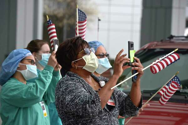 Orleen Dawes-Slater, center, and other Danbury Hospital employees photograph a 50 foot American flag that was set up at the hospital by Kyle DeLucia, owner of K&J Tree Service and his crew on a crane. They wanted to show their appreciation to the hospital staff serving the community during the covid pandemic. Tuesday, April 14, 2020, in Danbury, Conn.