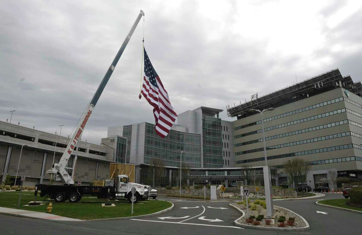 Kyle DeLucia, Owner of K&J Tree Service, and his crew set up a crane at the entrance to Danbury Hospital with a 50 foot American flag and a giant Thank You sign to show their appreciation to the hospital staff serving the community during the covid pandemic. Tuesday, April 14, 2020, in Danbury, Conn.