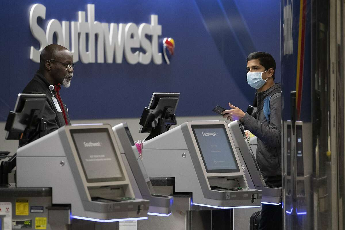 A Southwest Airlines employees helps a passenger wearing a facial mask at LaGuardia Airport, Saturday, March 21, 2020, in New York, N.Y. (AP Photo/Mary Altaffer)