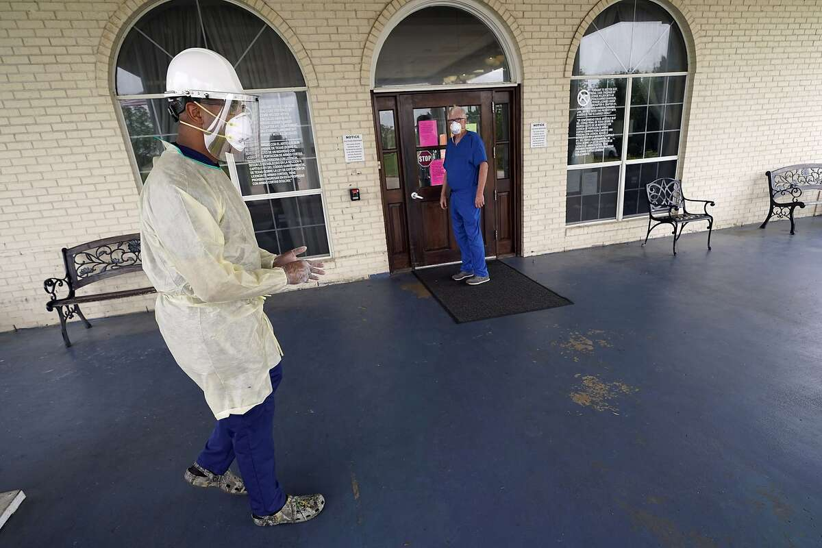 Dr. Robin Armstrong, left, prepares to enter The Resort at Texas City nursing home, where he is the medical director, Tuesday, April 7, 2020, in Texas City, Texas. Amrstrong said Tuesday it is too soon to tell whether the treatment is working. But his sweeping use of hydroxychloroquine at the nursing home illustrates how Trump's championing of the medication is having an impact on doctors across the U.S., even as scientists warn that more testing is needed before it's proven safe and effective against COVID-19. (AP Photo/David J. Phillip)
