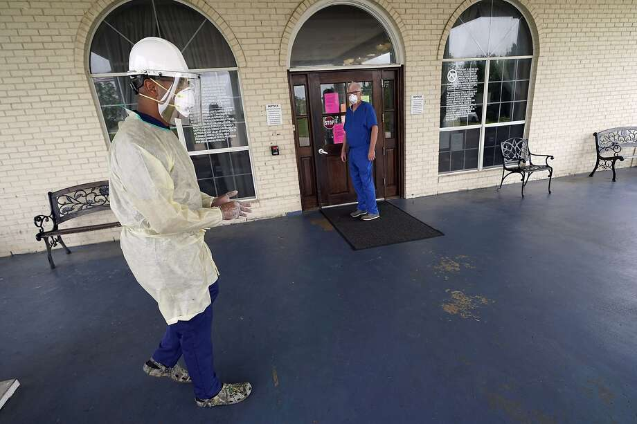 Dr. Robin Armstrong, left, prepares to enter The Resort at Texas City nursing home, where he is the medical director, Tuesday, April 7, 2020, in Texas City, Texas. Amrstrong said Tuesday it is too soon to tell whether the treatment is working. But his sweeping use of hydroxychloroquine at the nursing home illustrates how Trump's championing of the medication is having an impact on doctors across the U.S., even as scientists warn that more testing is needed before it's proven safe and effective against COVID-19. (AP Photo/David J. Phillip) Photo: David J. Phillip, Associated Press