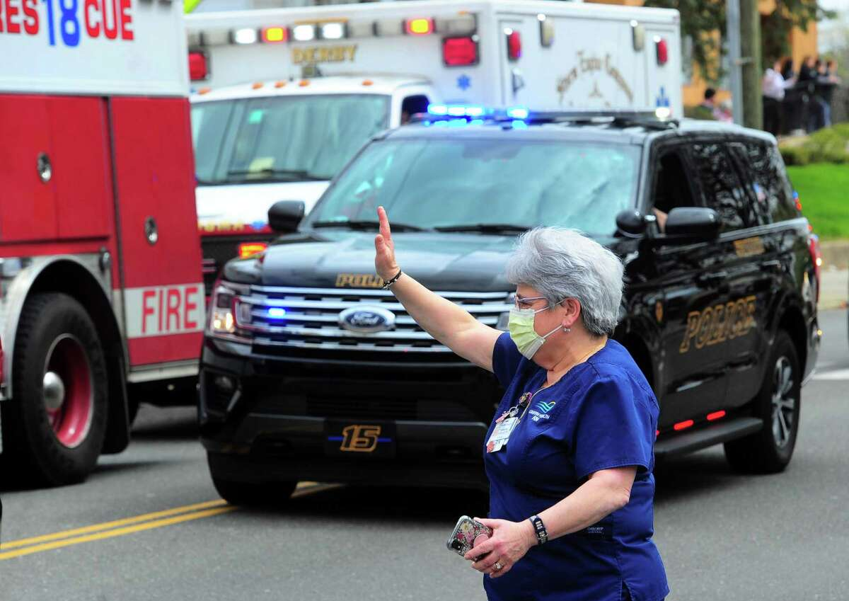 Griffin Hospital RN Adrienne Ziemkiewicz waves as dozens of fire, police, and EMS vehicles drive past as a thank you to their work in Derby, Conn., on Tuesday Apr. 14, 2020. Vehicles gathered at Nolan Field in Ansonia and rode in a parade along Wakelee Ave and then stopped briefly at the hospital to greet workers.