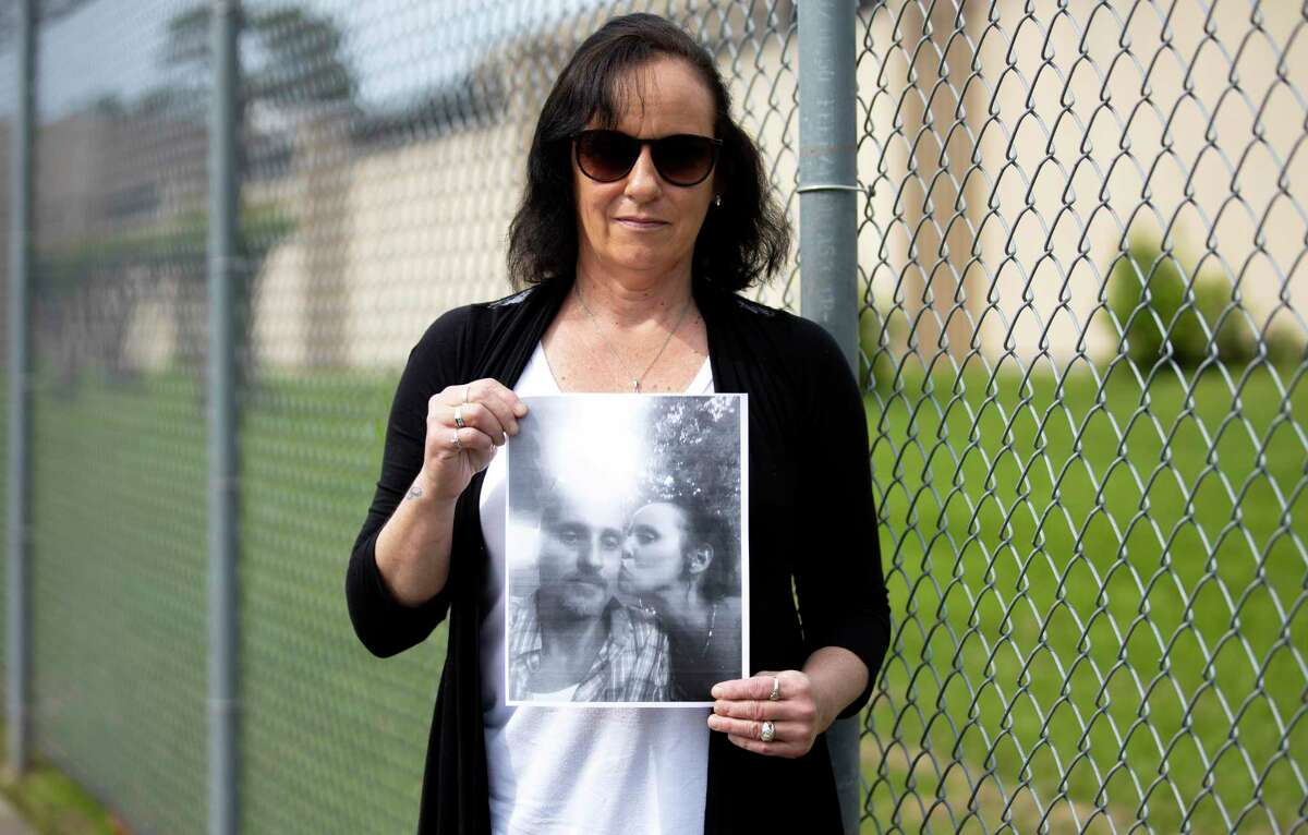 Tracey Schneider holds a printed image of her spouse outside of the Montgomery County jail in Conroe, Tuesday, April 7, 2020. Schneider fears that not enough is being done to prevent the spread of COVID-19 in the jail system.