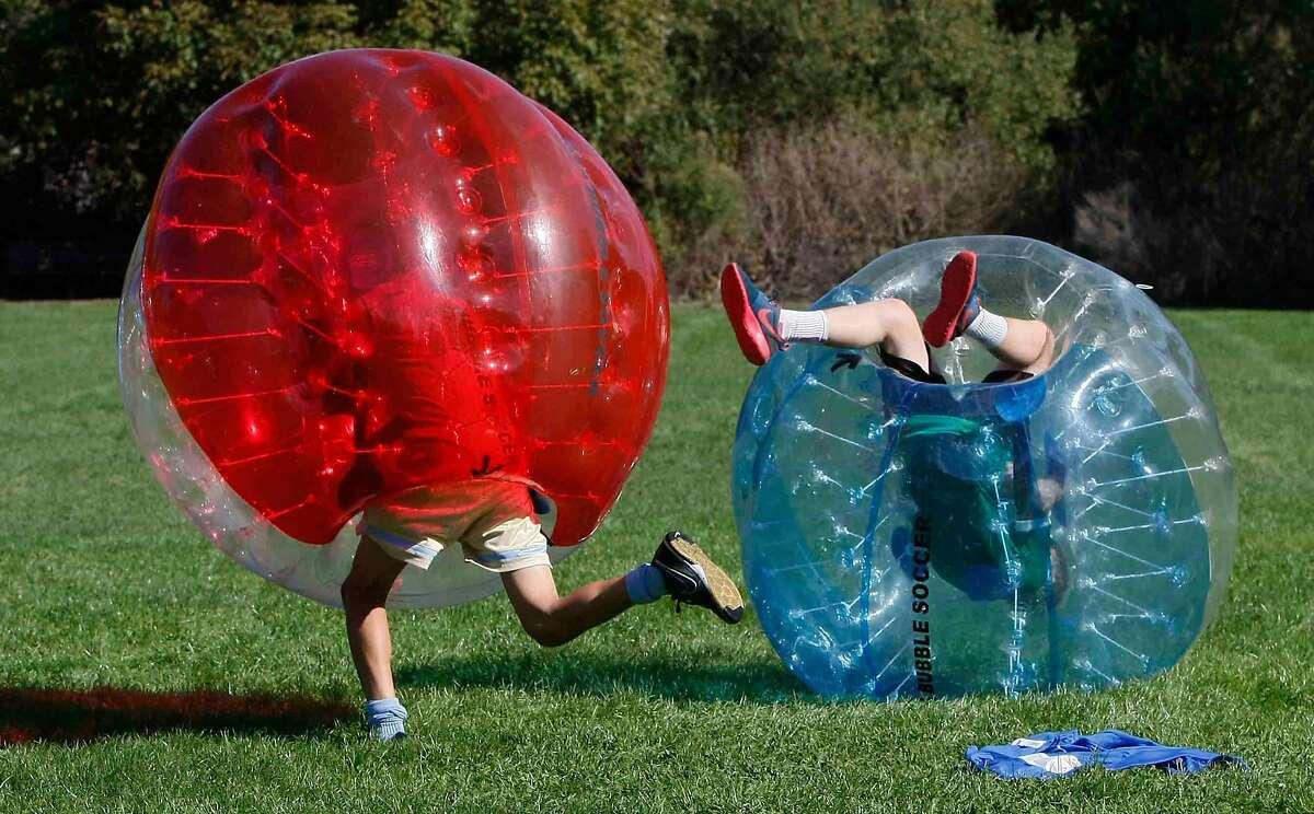 Members of Orinda's California Magic Soccer Club stumble over each other while playing bubble ball soccer at Rancho Laguna Park in Moraga, Calif. Sunday, November 2, 2014.