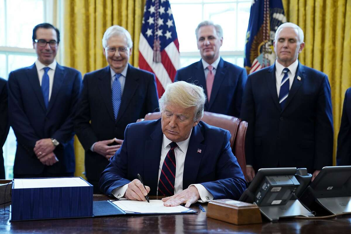FILE - In this March 27, 2020 file photo, President Donald Trump signs the coronavirus stimulus relief package, at the White House in Washington, as from left, Treasury Secretary Steven Mnuchin, Senate Majority Leader Mitch McConnell of Ky., House Minority Kevin McCarthy of Calif., and Vice President Mike Pence, look on. Beginning this month, Americans will see financial relief checks from the federal government's $2 trillion stimulus plan flow into their bank accounts to assist them during the COVID-19 outbreak. But many college students and recent graduates were disappointed to find out they will not receive $1,200 from the government, even if they were affected by the pandemic.(AP Photo/Evan Vucci, File)