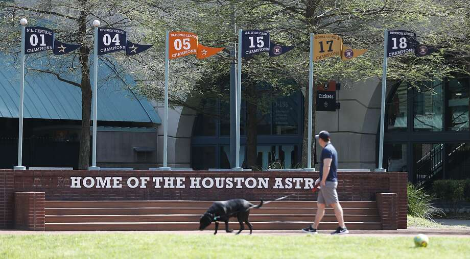 "Brian Duhon walks his dog, Charlie, at the Plaza at Minute Maid Park in Houston, Wednesday, March 25, 2020, one day after Harris County Judge Lina Hidalgo issued a ""stay at home, work safe"" order. Photo: Karen Warren, Staff Photographer"