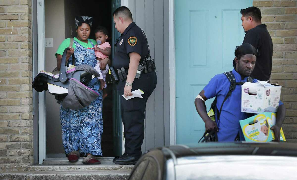 Bexar County Deputy Constable Edward Prado of Precinct 4 stands by as cohabitants of Patricia A White leave White's apartment after she is served a writ of possession at Brooks Townhomes on Wednesday, Nov. 6, 2019.