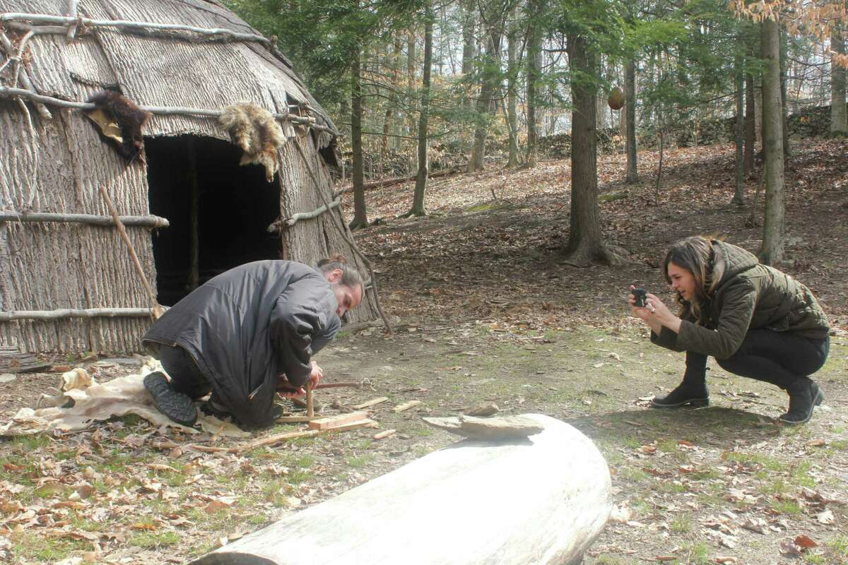 Educators at the The Institute for American Indian Studies Museum & Research Center in Washington, Conn., work on creating a short video about survival skills. Lauren Bennet is filming Griffin Kalin as he uses a bow fire-starter. The video will be part of a new series that was started as a way to connect with the public while the museum remains temporarily closed because of the pandemic.