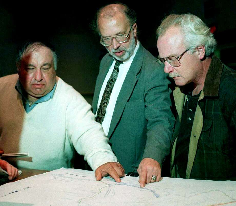 Longtime New Milford Conservation Commission member Michael-John Cavallaro, right, died April 8. He is shown above in this October 1998 photo with developer Tom Pilla, left, and Adam Halasi-Kun, center, chairman of the New Milford Conservation Commission, as the men look at proposed changes to the Still Meadow property prior to a town meeting. Photo: File Photo / The News-Times