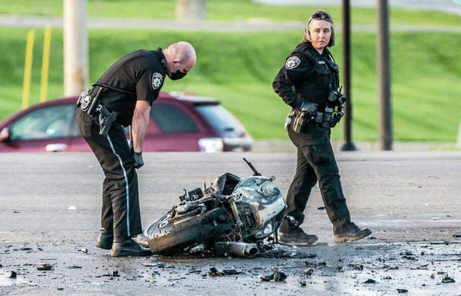 Alton Police officers examine the remains of a motorcycle that crashed and caught fire Tuesday night on Homer M. Adams Parkway.