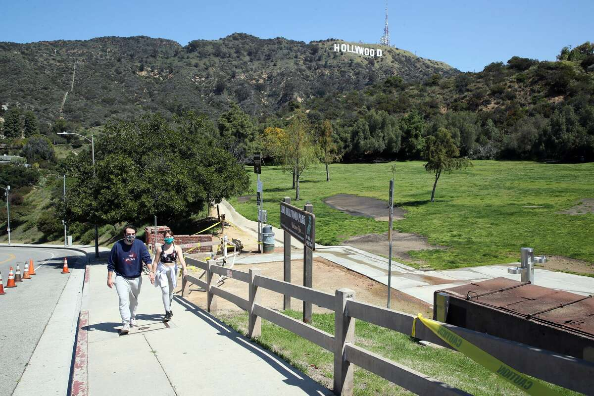Two people wearing protective face masks are seen walking with a view of the Hollywood Sign in the background on April 14, 2020 in Los Angeles. Los Angeles County has made wearing a mask mandatory for anyone entering an essential business.