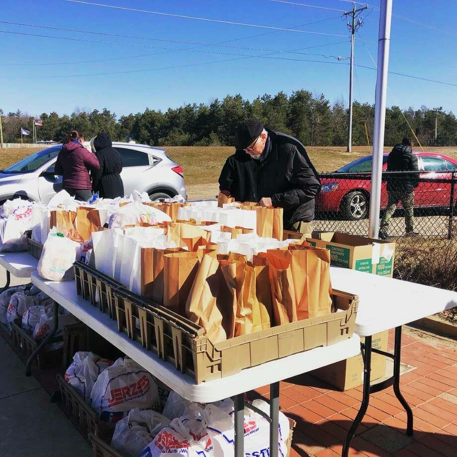 Volunteers with Fresh Wind Christian Community stage food bags to be put into cars at the drive-in food bank. (Courtesy Photo)