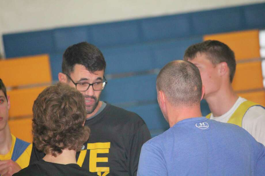 Evart boys basktball coach coach Kris Morgan (second from left) talks to his team after a practice this season. (Herald Review file photo)