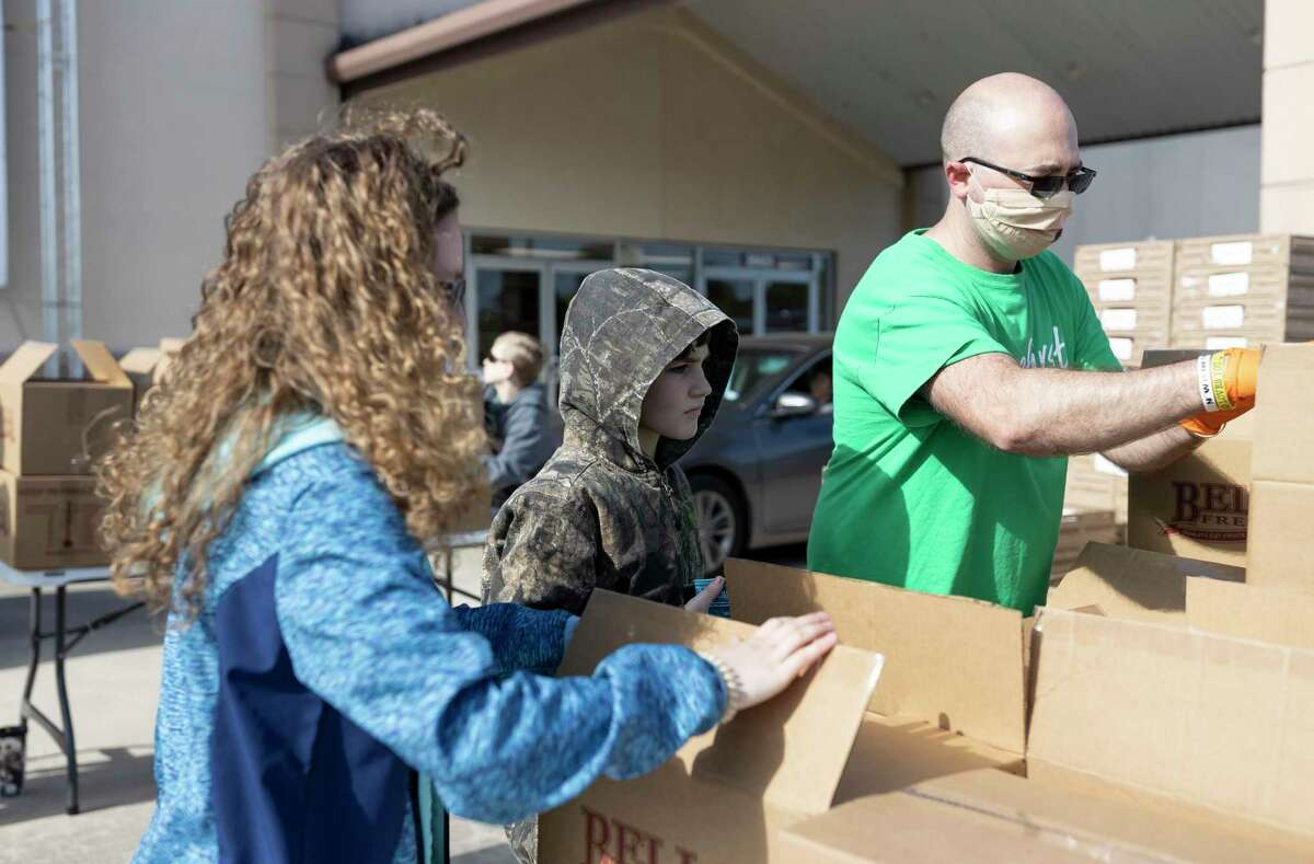 Karley and Devin Stanley assist a food drive coordinator at First Montgomery Baptist Church, Tuesday, April 14, 2020. Frequent trips to volunteer is a part of their established school routine.