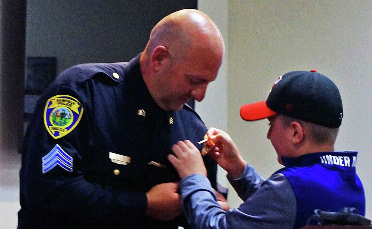 Landon Zdru pins a sergeant's badge on his father, Jeremy Zdru, at a promotional ceremony Monday at police headquarters.