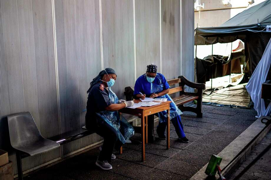 Health workers fill out documents before being tested for COVID-19 Photo: Getty Images / AFP or licensors