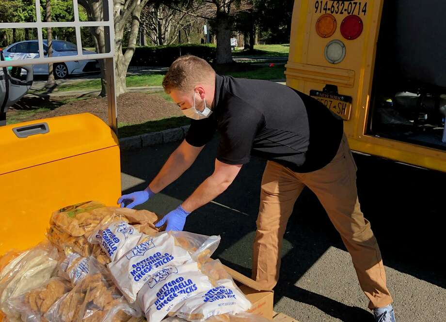 Assistant Director of the Iona Prep school campus, Justin Pellegrino, moves food onto a bus to deliver to Greenwich food pantry Neighbor to Neighbor. Photo: Contributed / Iona Preperatory School / Contributed Photo / Greenwich Time