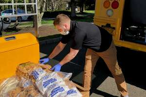 Assistant Director of the Iona Prep school campus, Justin Pellegrino, moves food onto a bus to deliver to Greenwich food pantry Neighbor to Neighbor.