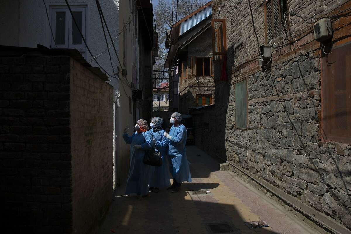 Kashmiri health workers prepares to enter a residential building during contact-tracing drive after the first person in the region was tested positive for COVID-19 in Srinagar, Indian controlled Kashmir, Thursday, March 19, 2020. For most people, the new coronavirus causes only mild or moderate symptoms. For some it can cause more severe illness. (AP Photo/ Dar Yasin)