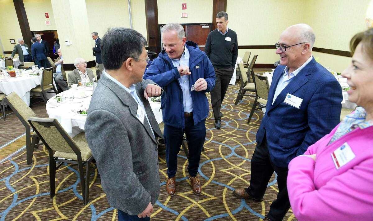 Attendees George Paik and Bill Catanzara elbow-bump each other as they prepare to listen to Dr. Sten Vermund of Yale School of Medicine discuss global warming and the coronavirus pandemic during a forum at the Stamford Sheraton hotel on March 11, 2020 in Stamford, Connecticut. The Stamford Sheraton announced April 13, 2020 that it was cutting about 100 positions amid the coronavirus crisis.