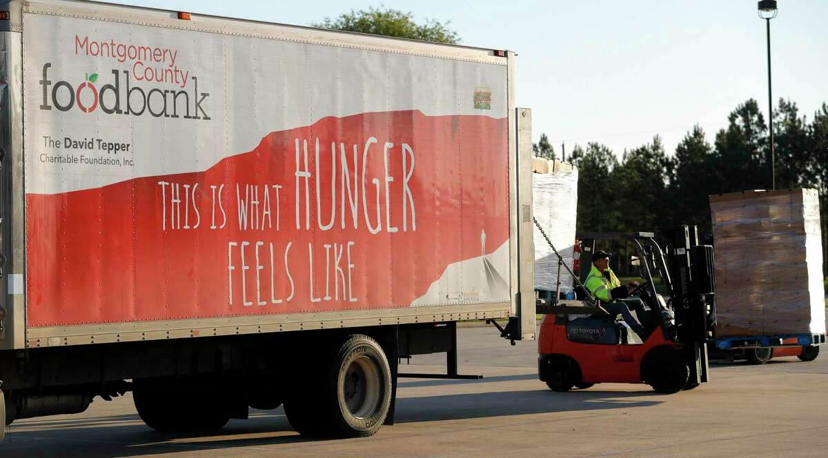 A pallet of food is unloaded from the Montgomery County Food Bank trailer as the Community Assistance Center distributes food to 500 families at The Ark Church, Wednesday, April 15, 2020, in Conroe. The food bank was granted $80,000 this month from the Greater Houston COVID-19 Recovery Fund to purchase food staples and feed 100,000 families.