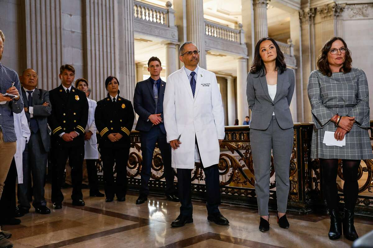 Doctor Tomas Aragon (center) looks on as San Francisco Mayor London Breed announces a state of emergency due to the global outbreak of the coronavirus during a press conference at City Hall on Tuesday, Feb. 25, 2020 in San Francisco, California.
