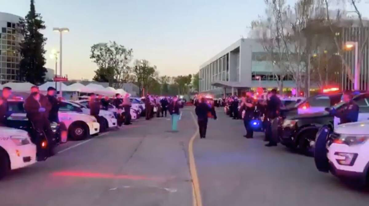 Police officers and fire officials greet medical staff on theirway into work at the Valley Medical Center in San Jose.