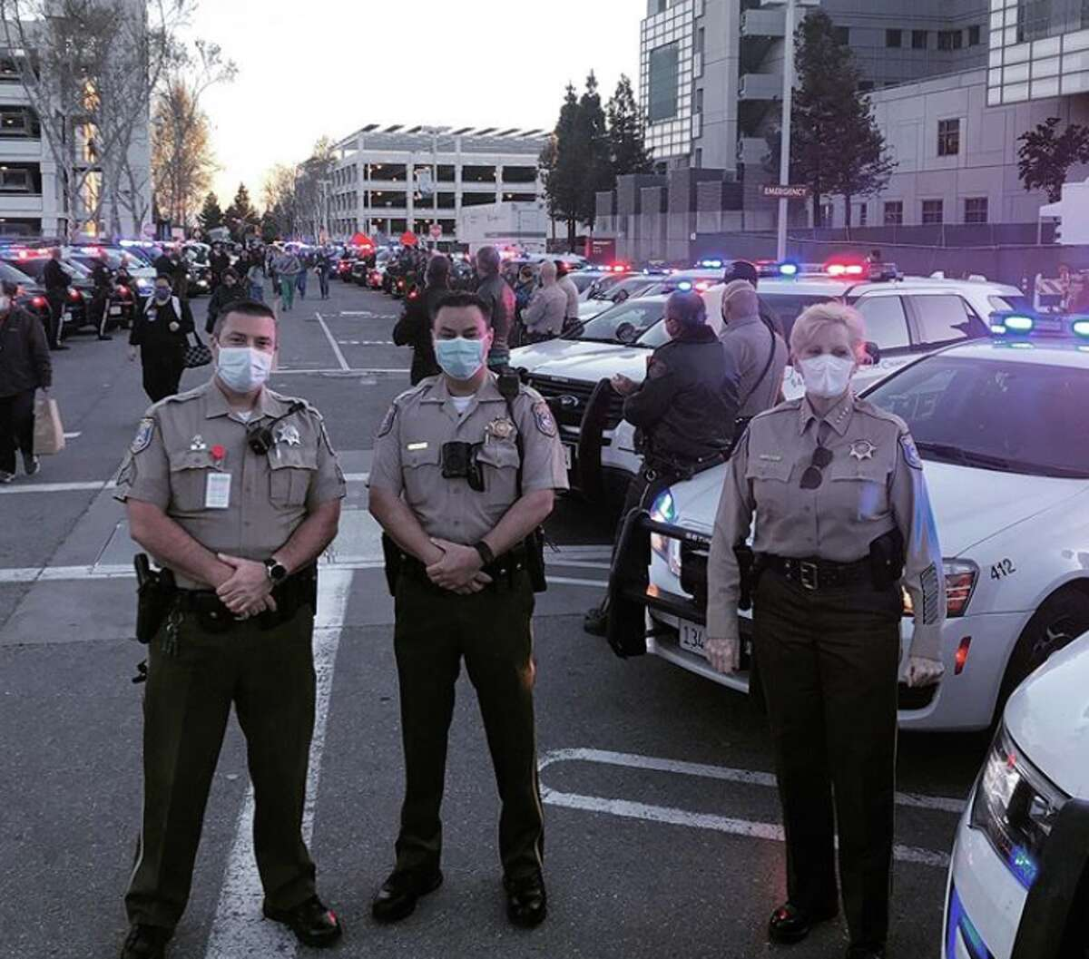 Police officers and fire officials greet medical staff on their way into work at the Valley Medical Center in San Jose.