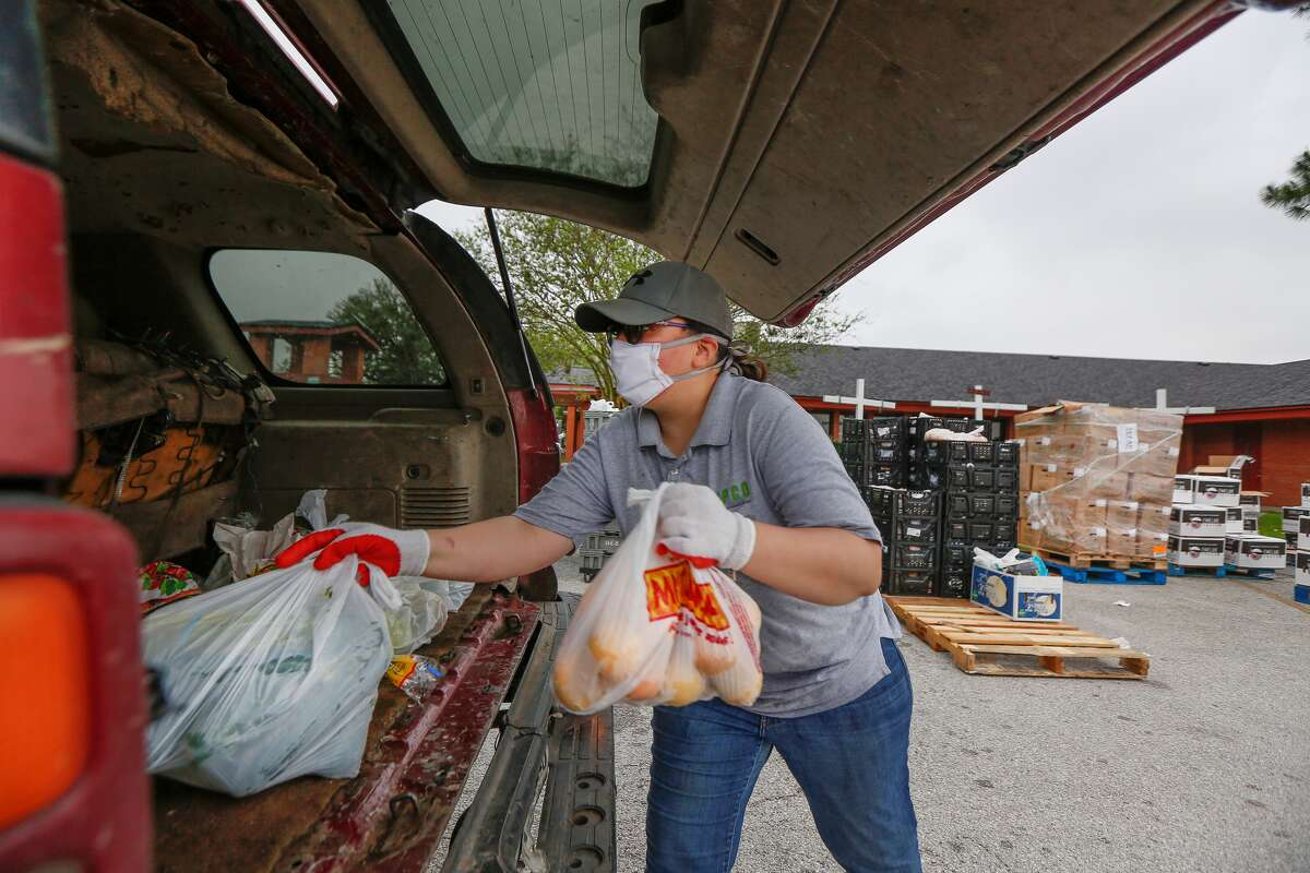 Celia Curiel carga bolsas con alimentos a un vehículo de una persona que se acercó a pedir ayuda en la iglesia de San Pedro, de Pasadena, en las afueras de Houston, el miércoles 8 de abril de 2020.
