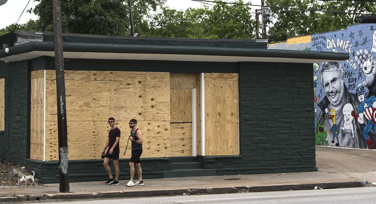 People walk past a boarded up business on Westheimer in the Montrose area on Saturday, March 28, 2020 in Houston. Businesses around the city have been closed and boarded up due to the coronavirus pandemic precautions, forcing several businesses to shut their doors.